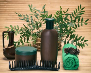 Natural hair treatment products, comb and towel with coniferous cones against the background of green plant branches in wooden basket